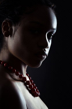 Magdalena Russocka young african woman with red coral necklace in shadow inside