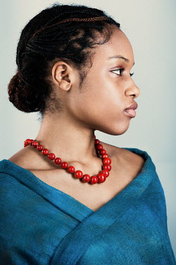Magdalena Russocka young african woman with red coral necklace wrapped with blue shawl inside