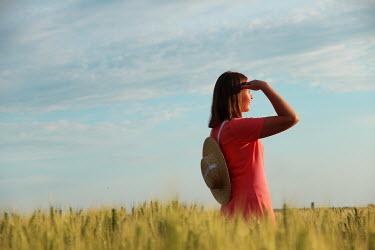 Jasenka Arbanas WOMAN WITH STRAW HAT STANDING IN FIELD