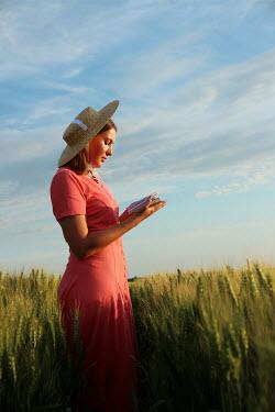 Jasenka Arbanas WOMAN WITH STRAW HAT READING IN FIELD