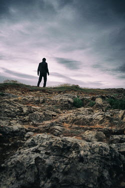Tim Robinson SILHOUETTED MAN IN ROCKY COUNTRYSIDE AT DUSK