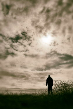 Tim Robinson SILHOUETTED MAN STANDING IN COUNTRYSIDE AT DUSK