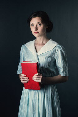 Magdalena Russocka young retro woman holding book standing inside