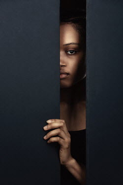 Magdalena Russocka young african woman staring through gap in wall