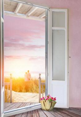 Sandra Cunningham COUPLE ON SUNLIT BEACH WITH BEACH HOUSE