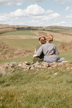 Shelley Richmond TWO RETRO WOMAN HUGGING ON WALL IN COUNTRYSIDE