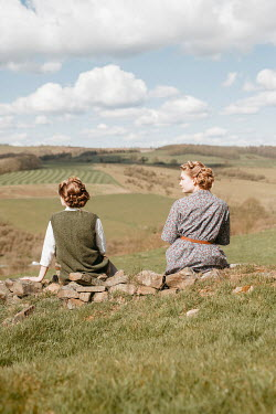 Shelley Richmond TWO RETRO WOMAN SITTING ON WALL IN COUNTRYSIDE