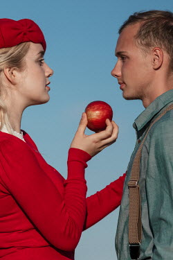 Magdalena Russocka close up of retro man and woman holding apple outside