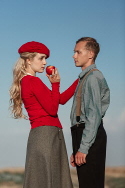 Magdalena Russocka close up of retro man and woman holding apple in field