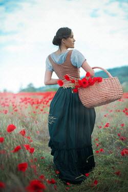 Ildiko Neer Historical woman walking in meadow with basket