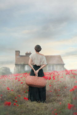 Ildiko Neer HISTORICAL WOMAN CARRYING BASKET IN POPPY FIELD WITH HOUSE