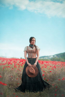 Ildiko Neer Historical woman holding cowboy hat countryside