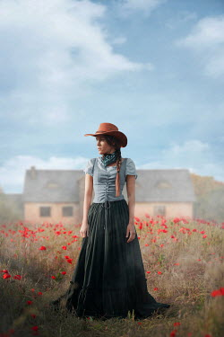 Ildiko Neer Historical woman in cowboy hat standing countryside by house