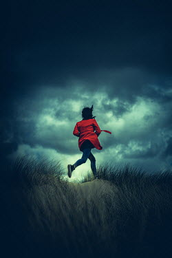 Marie Carr WOMAN WITH RED COAT RUNNING IN STORMY SAND DUNES
