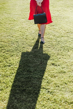 Matilda Delves RETRO WOMAN IN RED DRESS OUTDOORS WITH SHADOW