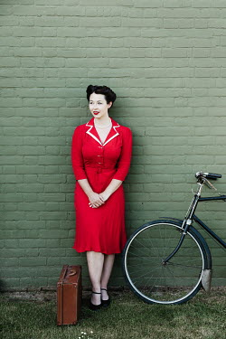 Matilda Delves RETRO WOMAN OUTDOORS WITH SUITCASE AND BICYCLE