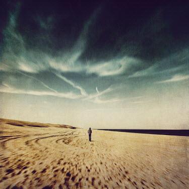 Dirk Wustenhagen MAN IN HOOD WALKING ON SANDY BEACH