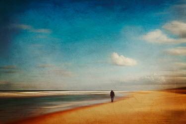 Dirk Wustenhagen MAN WALKING ON SANDY BEACH WITH BLUE SKY