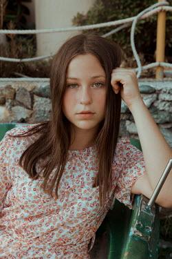 Greta Larosa YOUNG GIRL WITH BROWN HAIR SITTING OUTSIDE