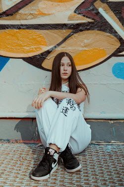 Greta Larosa YOUNG GIRL SITTING BY WALL WITH GRAFFITI