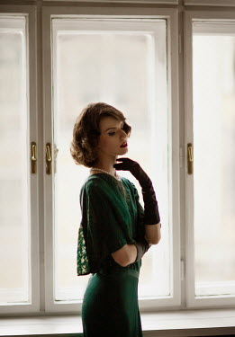 Nikaa BRUNETTE WOMAN WITH GLOVES INDOORS BY WINDOW