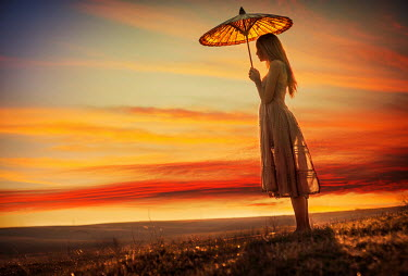 Metin Demiralay WOMAN WITH PARASOL IN LANDSCAPE AT SUNSET