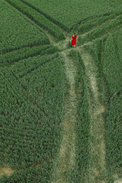 Maria Petkova WOMAN IN RED DRESS STANDING IN FIELD WITH TRACKS