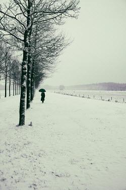 Yolande de Kort MAN WITH UMBRELLA IN SNOWY LANDSCAPE