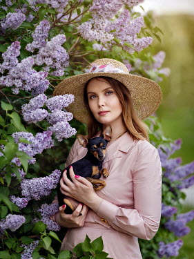 Alexey Kazantsev WOMAN IN HAT HOLDING DOG IN GARDEN