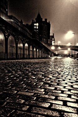 Laurence Winram COBBLED STREET WITH ARCHES AND BRIDGE AT NIGHT