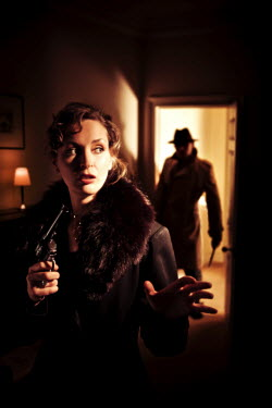 Laurence Winram ARMED WOMAN AND MAN IN DIM LIT ROOM
