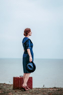 Natasza Fiedotjew Vintage woman holding hat standing on cliff by sea with suitcase
