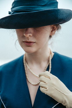 Natasza Fiedotjew Close up of vintage woman in hat holding pearl necklace with gloved hand