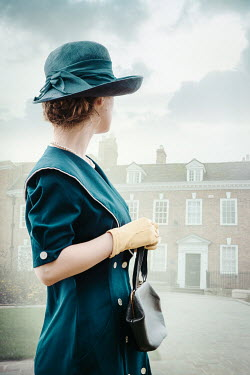 Natasza Fiedotjew Vintage woman in hat holding purse looking at front door