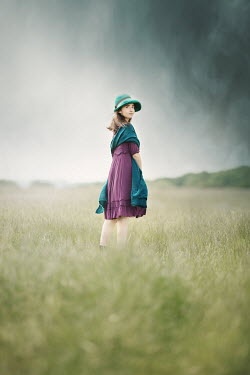 Anna Buczek GIRL WITH HAT STANDING IN FIELD