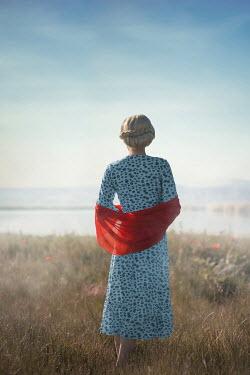 Ildiko Neer Blonde woman standing in meadow by lake