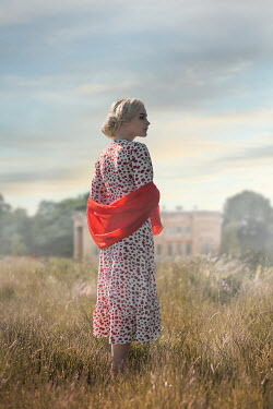 Ildiko Neer Blonde woman standing in meadow by house