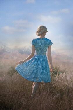 Ildiko Neer Blonde woman standing in field by mountains
