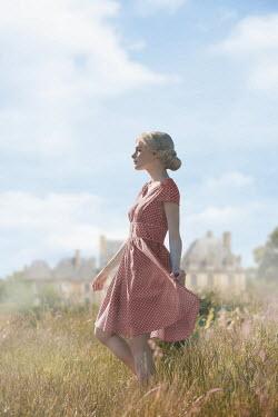 Ildiko Neer Blonde woman walking in grass by house