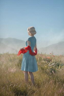 Ildiko Neer Blonde woman standing in meadow by hills