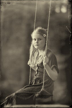 Laurence Winram SAD GIRL ON SWING WITH FLOWER