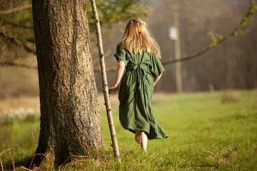 Laurence Winram GIRL IN GREEN DRESS RUNNING IN FIELD