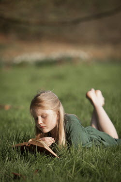 Laurence Winram GIRL READING BOOK IN GREEN DRESS ON GRASS