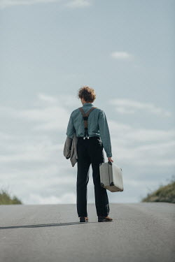 Magdalena Russocka retro man with suitcase standing on country road
