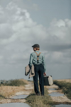 Magdalena Russocka retro man with suitcase standing on dirt road in fields