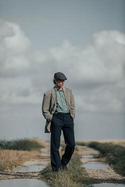 Magdalena Russocka retro man walking on dirt road in fields