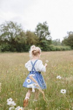 Shelley Richmond LITTLE GIRL HOLDING FLOWER WALKING IN FIELD