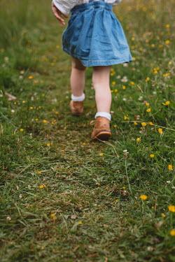 Shelley Richmond LITTLE GIRL IN DENIM SKIRT WALKING IN FIELD