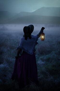 Natasza Fiedotjew Historical woman in bonnet holding lantern in foggy valley at dusk
