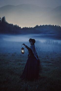 Natasza Fiedotjew Historical woman holding lantern in countryside at dusk